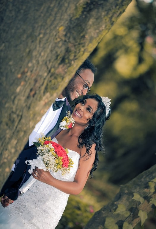 Noivos sorrindo; noiva de cabelo ondulado, solto, com coroa