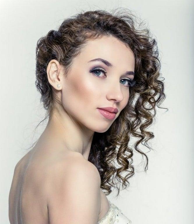 Mulher com cabelo ondulado, solto, de lado