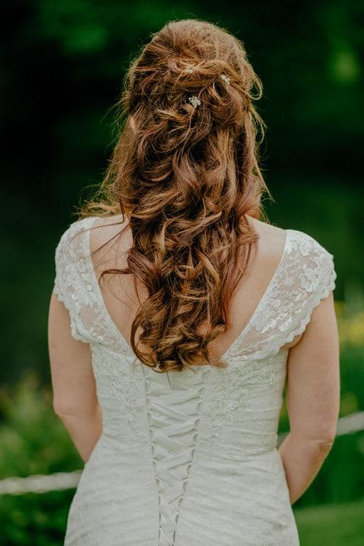 Mulher de cabelo ondulado, longo, com penteado semi preso