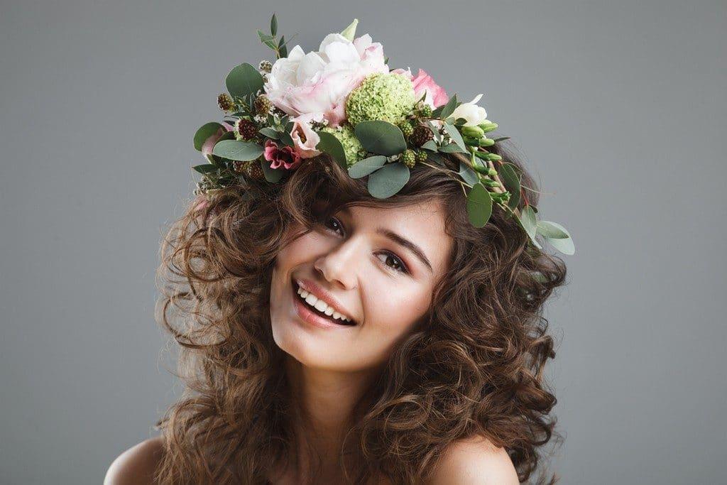 Mulher de cabelo ondulado, solto, com arranjo de flores