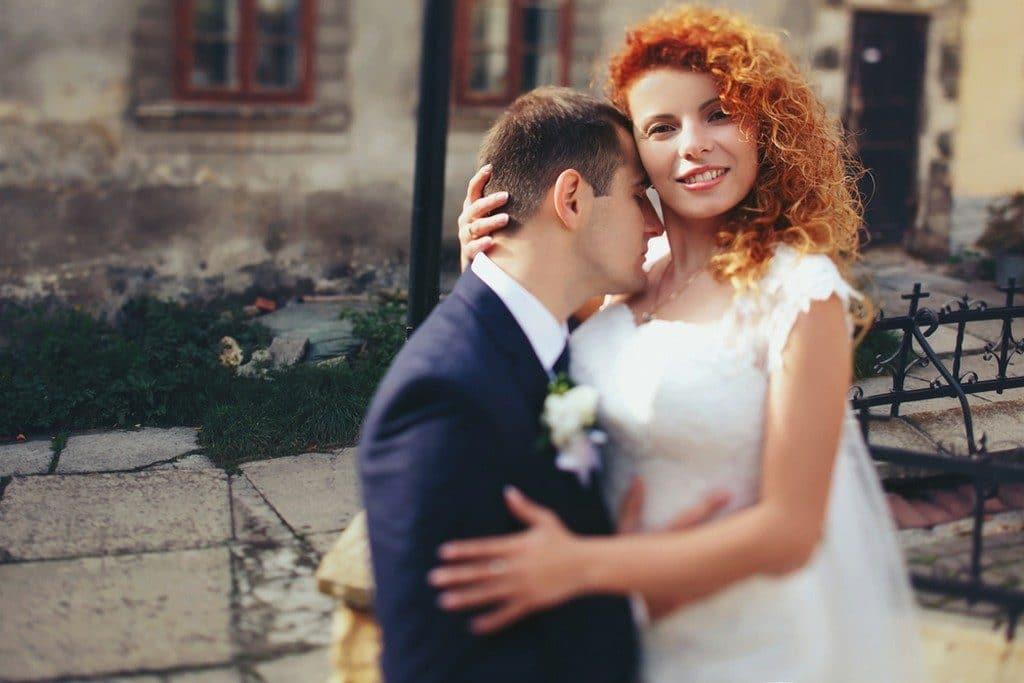 Noivos se abraçando; noiva de cabelo cacheado, médio, solto, de lado