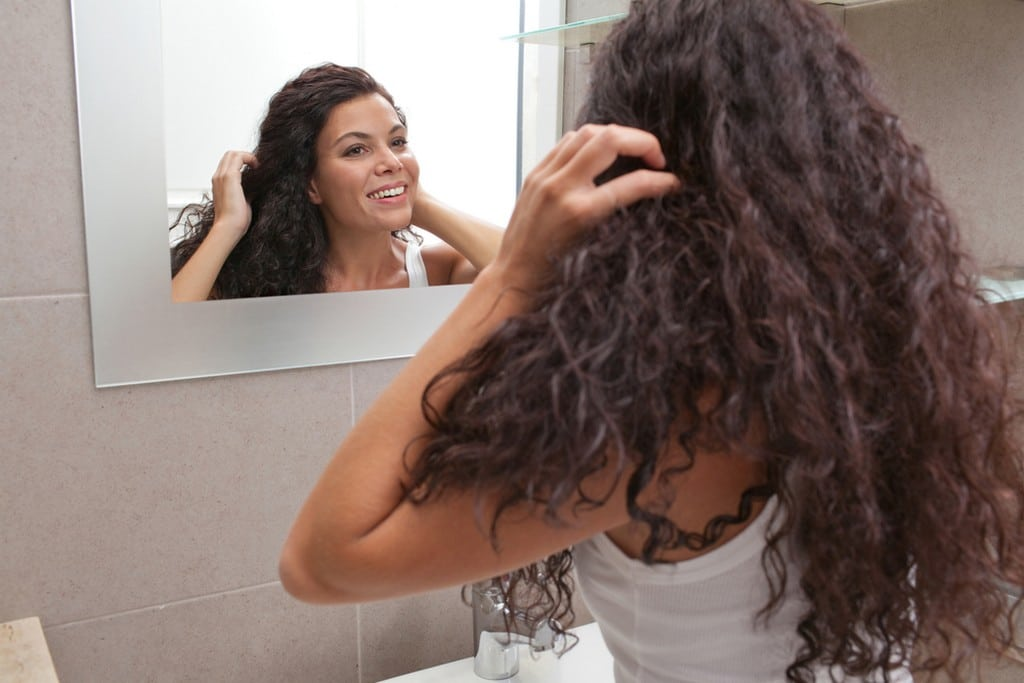 Mulher de cabelo cacheado se olhando no espelho