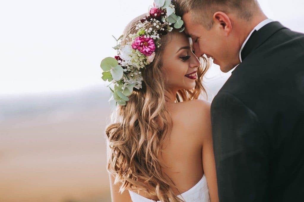 Noivos se olhando; noiva de cabelo ondulado, longo, solto, com tiara de flores
