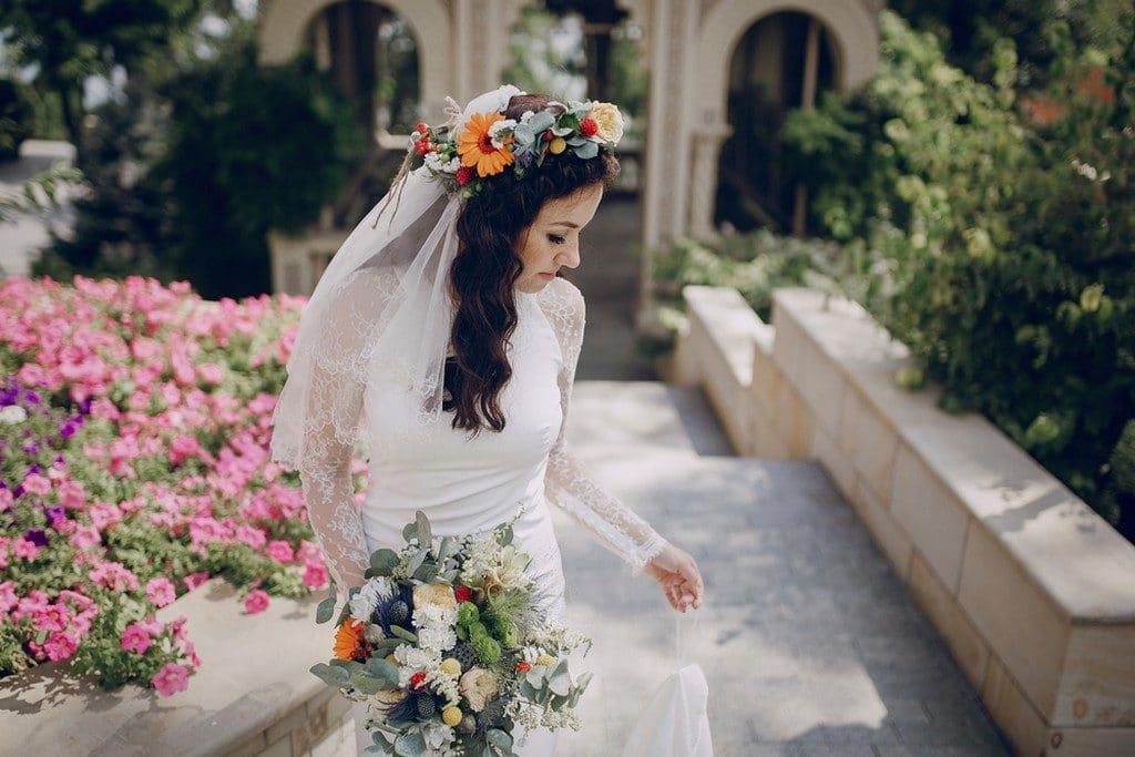 Noiva de cabelo ondulado, solto, com véu e coroa de flores