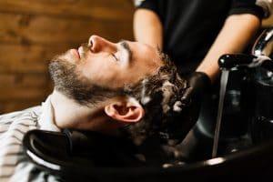 Homem lavando o cabelo no salão de beleza