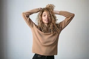 Mulher de cabelo cacheado, tamanho médio, com corte em camadas