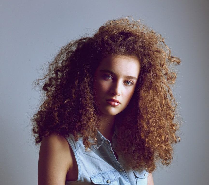 Mulher de cabelo cacheado, com corte repicado