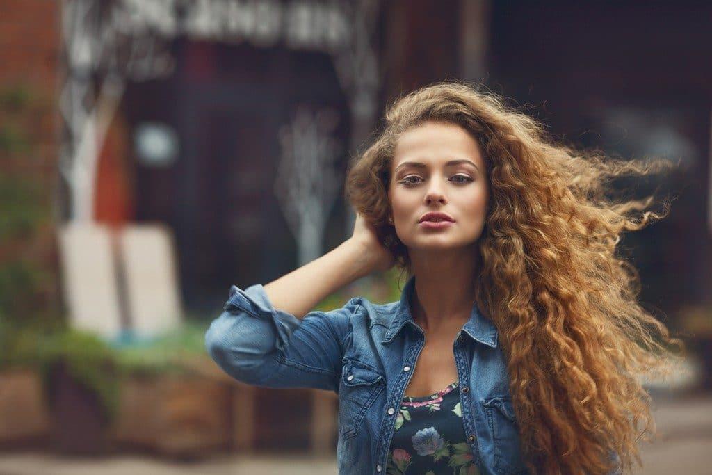 Mulher de cabelo ondulado, com corte para dar volume, longo
