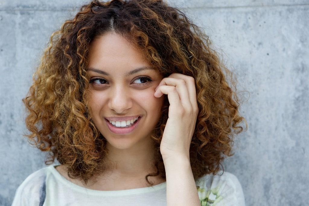Mulher de cabelo cacheado, com corte curto/médio