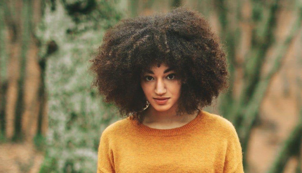 Mulher jovem com corte curto para cabelo crespo
