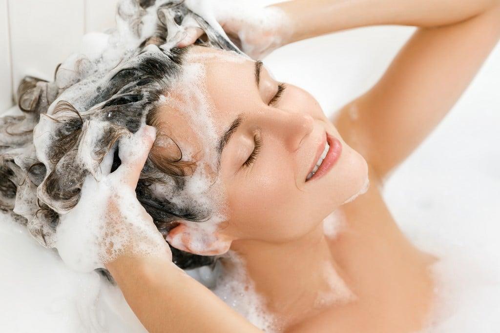 Mulher lavando o próprio cabelo