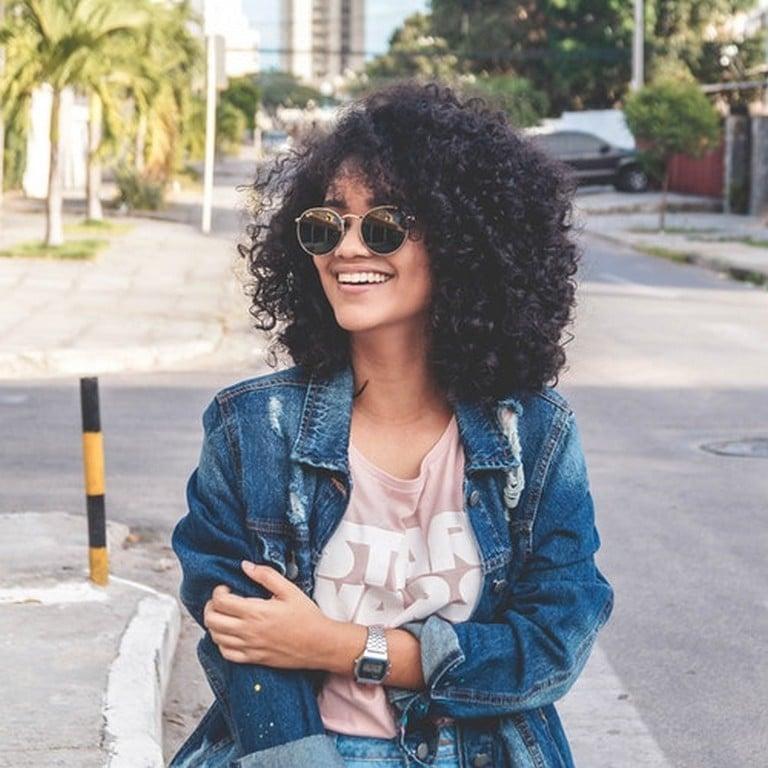 Mulher de cabelo cacheado preto sorrindo