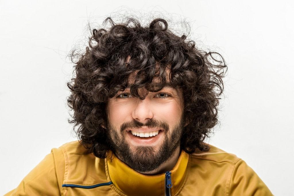 Homem com cabelo ondulado, com corte repicado com franja desconectada