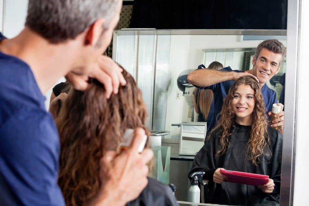 Mulher de cabelo cacheado, cortando os fios com um profissional