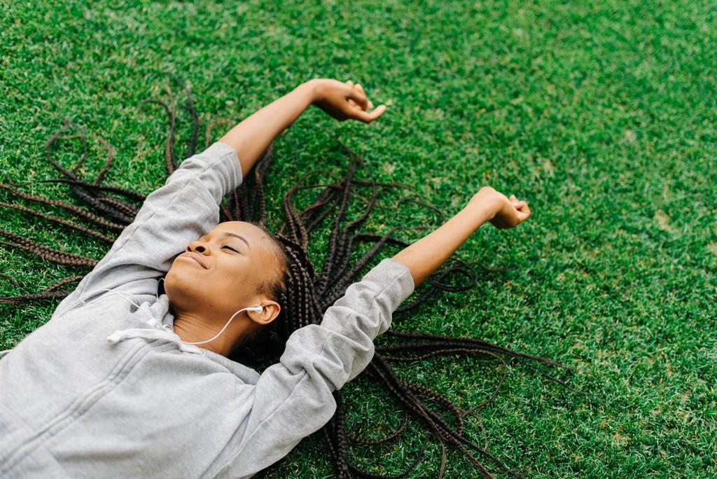 Mulher jovem, com trança, deitada na grama