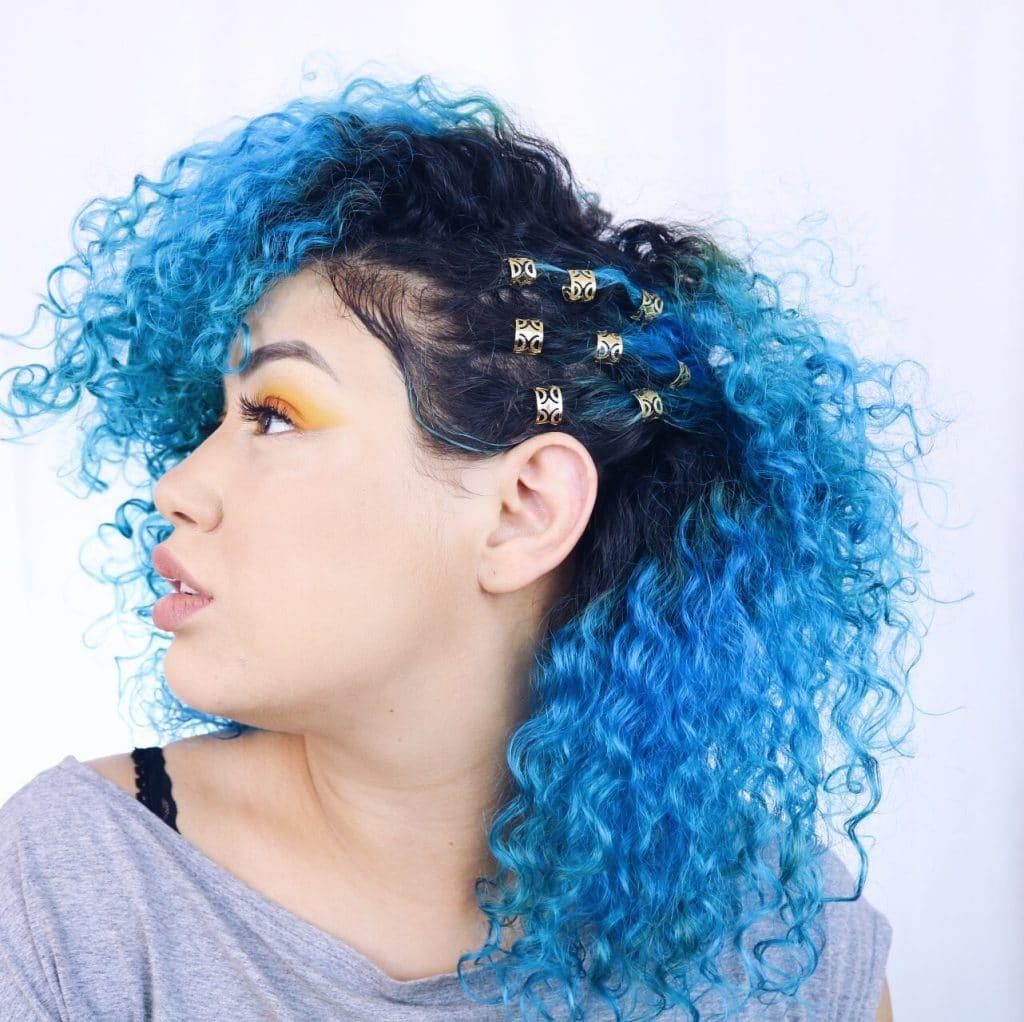 mulher de perfil com cabelo azul e raiz preta
