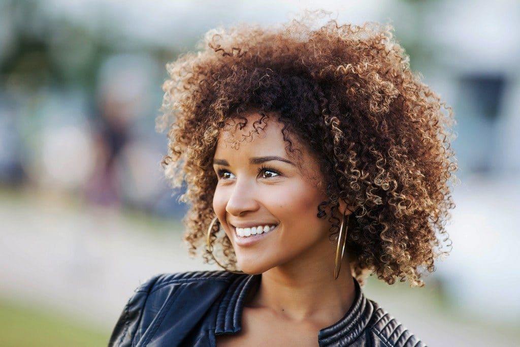 Mulher de cabelo cacheado com corte assimétrico