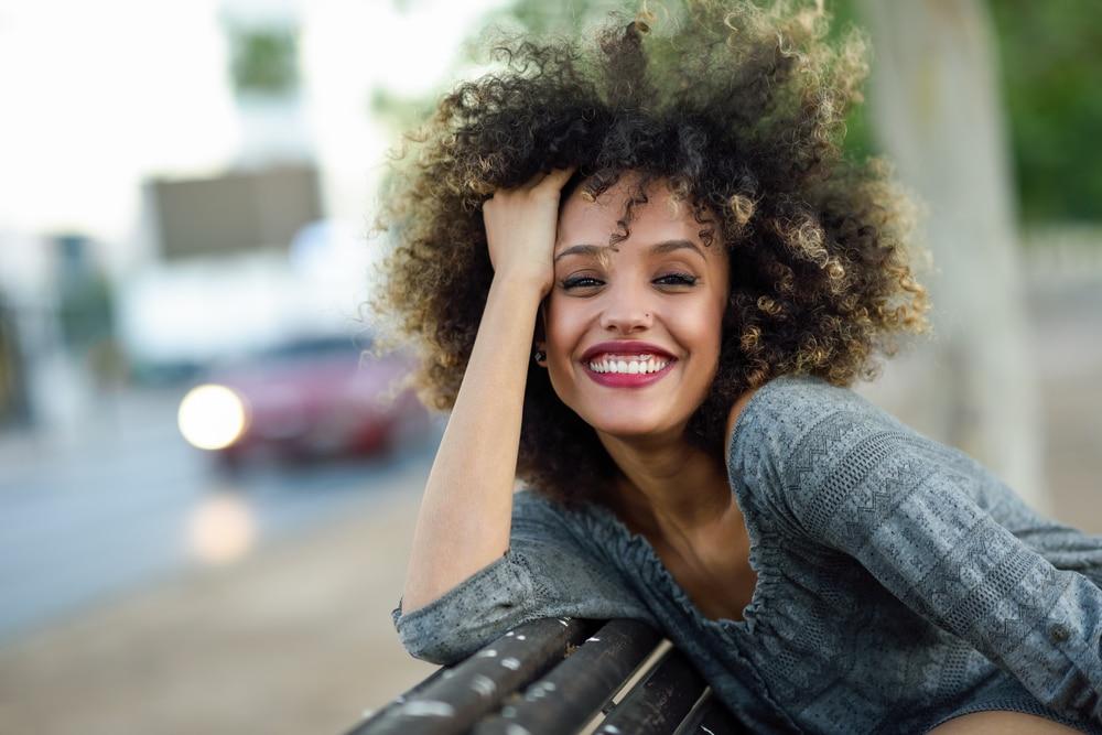 Mulher com corte de cabelo cacheado curto